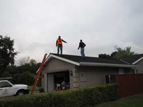 Installation crew starts measuring roof to mark for layout